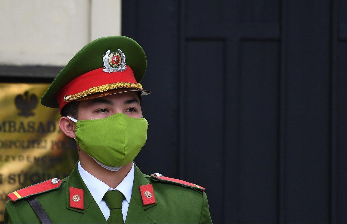 A Vietnamese policeman wearing a protective face mask